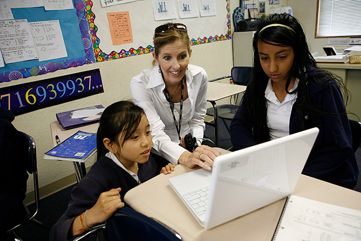 Female teacher works with girls at computer