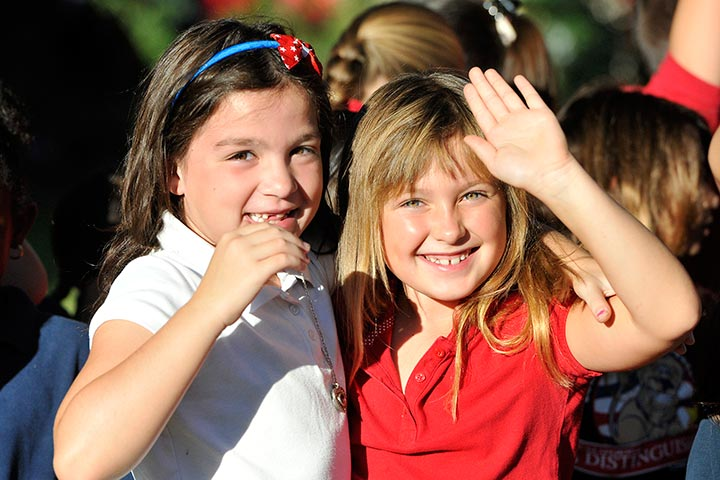 Two elementary girls wave
