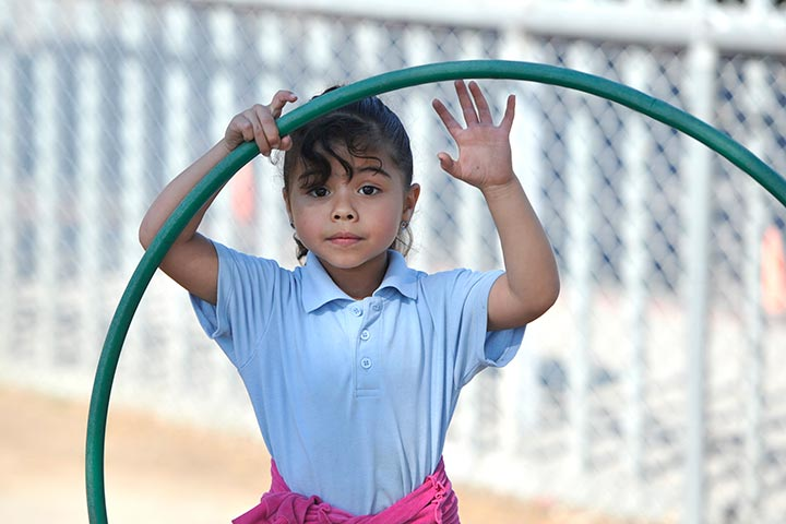 Elementary girl plays with hoop